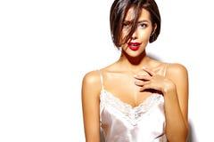 Bella donna castana sexy sveglia felice con le labbra rosse in biancheria dei pigiami su fondo bianco Fotografie Stock Libere da Diritti