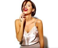 Bella donna castana sexy sveglia felice con le labbra rosse in biancheria dei pigiami su fondo bianco Immagine Stock Libera da Diritti
