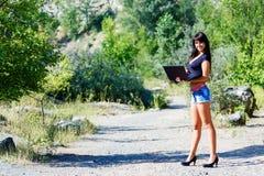 Bella donna castana sorridente che lavora con un computer portatile all'aperto Fotografia Stock Libera da Diritti