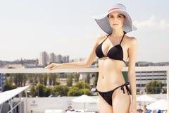 Bella donna castana sulla spiaggia nel rilassamento solo dello stagno dentro Immagine Stock