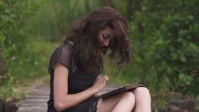 Bella donna castana in vestito nero elegante facendo uso della compressa digitale mentre sedendosi su un pilastro di legno nel gi video d archivio