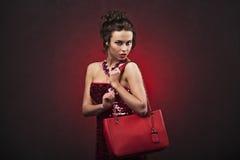 Bella donna castana in vestito rosso con trucco professionale e nell'acconciatura con la grande collana che tiene borsa rossa Immagine Stock