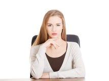 Bella donna casuale che si siede da uno scrittorio. Fotografia Stock