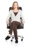 Bella donna casuale che si siede su una sedia. Immagini Stock