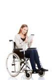 Bella donna casuale che si siede sulla sedia a rotelle di w con la compressa. Immagini Stock Libere da Diritti