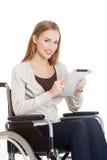 Bella donna casuale che si siede sulla sedia a rotelle di w con la compressa. Fotografia Stock Libera da Diritti