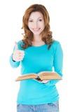 Bella donna casuale che tiene un libro e che mostra OKAY. Fotografia Stock