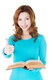 Bella donna casuale che tiene un libro e che mostra OKAY. Immagini Stock Libere da Diritti