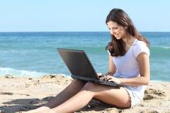 Bella donna con un computer portatile sulla spiaggia Fotografie Stock Libere da Diritti