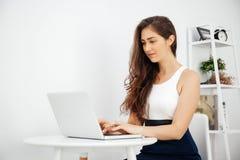 Bella donna caucasica che lavora al computer portatile sullo scrittorio bianco sopra fondo bianco con lo spazio della copia Immagine Stock