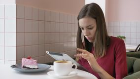 Bella donna caucasica elegante che per mezzo del computer della compressa, mandare un sms, scrivente Sorridendo nei fps del caffè archivi video