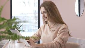 Bella donna caucasica elegante che per mezzo del computer della compressa, mandare un sms, scrivente Sorridendo nei fps del caffè stock footage