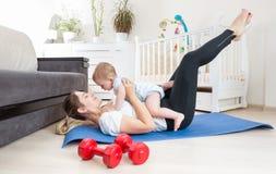 Bella donna che allunga sul pavimento e che tiene il suo neonato Fotografia Stock