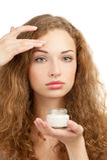 Bella donna che applica crema d'idratazione Immagine Stock