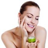Bella donna che applica la crema del moisturizer Fotografia Stock