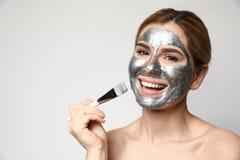Bella donna che applica maschera sul fronte contro il fondo leggero fotografia stock