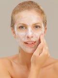 Bella donna che applica moisturizer sul suo fronte Fotografie Stock