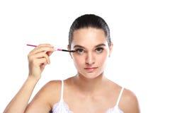 Bella donna che applica una certa mascara Fotografia Stock