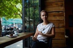 Bella donna che aspetta una chiamata sul telefono delle cellule mentre sedendosi da solo in caffè accogliente durante il tempo di Immagine Stock Libera da Diritti