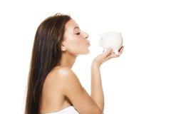 Bella donna che bacia una banca piggy Immagini Stock