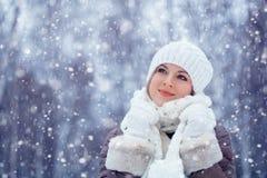 Bella donna che cammina all'aperto nell'ambito delle precipitazioni nevose fotografia stock