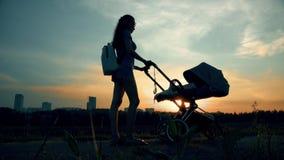 Bella donna che cammina con un passeggiatore nel parco della città al tramonto stock footage