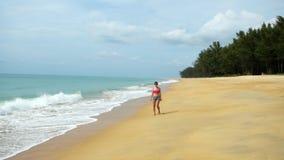 Bella donna che cammina lungo la linea costiera, le gambe della ragazza nella schiuma dell'acqua, mare tropicale Giorno pacifico  stock footage