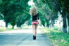 Bella donna che cammina su una strada campestre Fotografia Stock Libera da Diritti