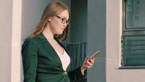 Bella donna che cammina sulla via della città e che guarda telefono cellulare video d archivio