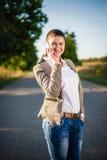 Bella donna che chiama qualcuno mentre camminando lungo la strada fotografia stock libera da diritti