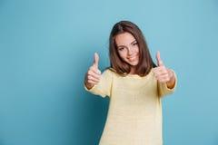 Bella donna che dà i pollici su sopra fondo blu Fotografia Stock