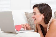Bella donna che data online sul computer portatile immagini stock