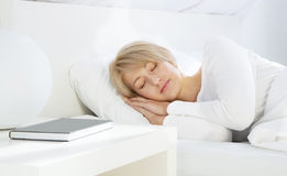 Bella donna che dorme nella base bianca Immagine Stock