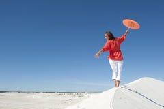Bella donna che equilibra sull'orlo della duna di sabbia Fotografie Stock Libere da Diritti