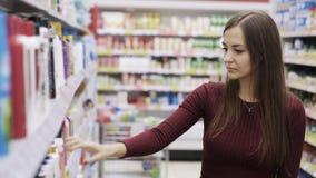 Bella donna che esamina i cosmetici in supermercato archivi video