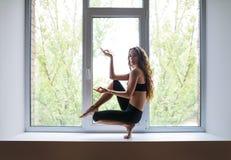 Bella donna che fa asana di yoga sul davanzale della finestra Immagini Stock Libere da Diritti