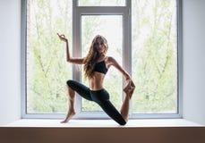 Bella donna che fa asana di yoga sul davanzale della finestra Immagine Stock