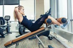 Bella donna che fa esercizio di forma fisica della stampa alla palestra di sport Immagine Stock