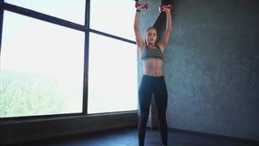 Bella donna che fa forma fisica Lei teste di legno di sollevamento nella palestra Addestramento di sport archivi video