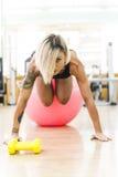 Bella donna che fa gli esercizi alla palestra con la palla di forma fisica Immagine Stock