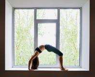 Bella donna che fa posa ascendente della ruota dell'arco di asana di yoga su vento Fotografia Stock Libera da Diritti