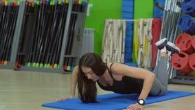 Bella donna che fa spinta-UPS sulla stuoia di esercizio nel corridoio di forma fisica stock footage
