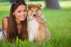 Bella donna che gioca nel parco con le collie del cucciolo fotografia stock libera da diritti