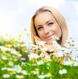 Bella donna che gode del campo e del cielo blu della margherita Fotografia Stock Libera da Diritti