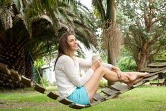 Bella donna che gode della tazza di caffè sull'amaca all'aperto Fotografia Stock Libera da Diritti