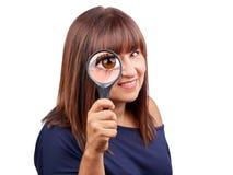 Bella donna che guarda tramite la lente d'ingrandimento isolata Immagine Stock