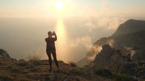 Bella donna che ha video chiacchierata facendo uso dello smartphone all'aperto contro il bello tramonto drammatico sopra un mare  video d archivio
