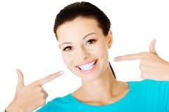 Bella donna che indica sui suoi denti bianchi perfetti. Fotografia Stock