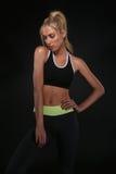 Bella donna che indossa l'abbigliamento sexy di allenamento sul nero Immagini Stock