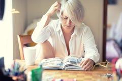 Bella donna che legge un libro a casa che si siede alla tavola accanto ad una finestra enorme un giorno caldo soleggiato Immagine Stock